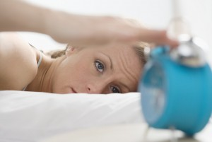 Woman Turning Off Alarm --- Image by © Royalty-Free/Corbis