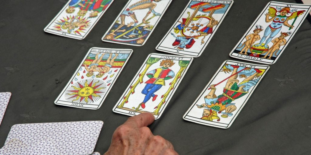 a reader's hand during the reading of the playing cards and Tarot